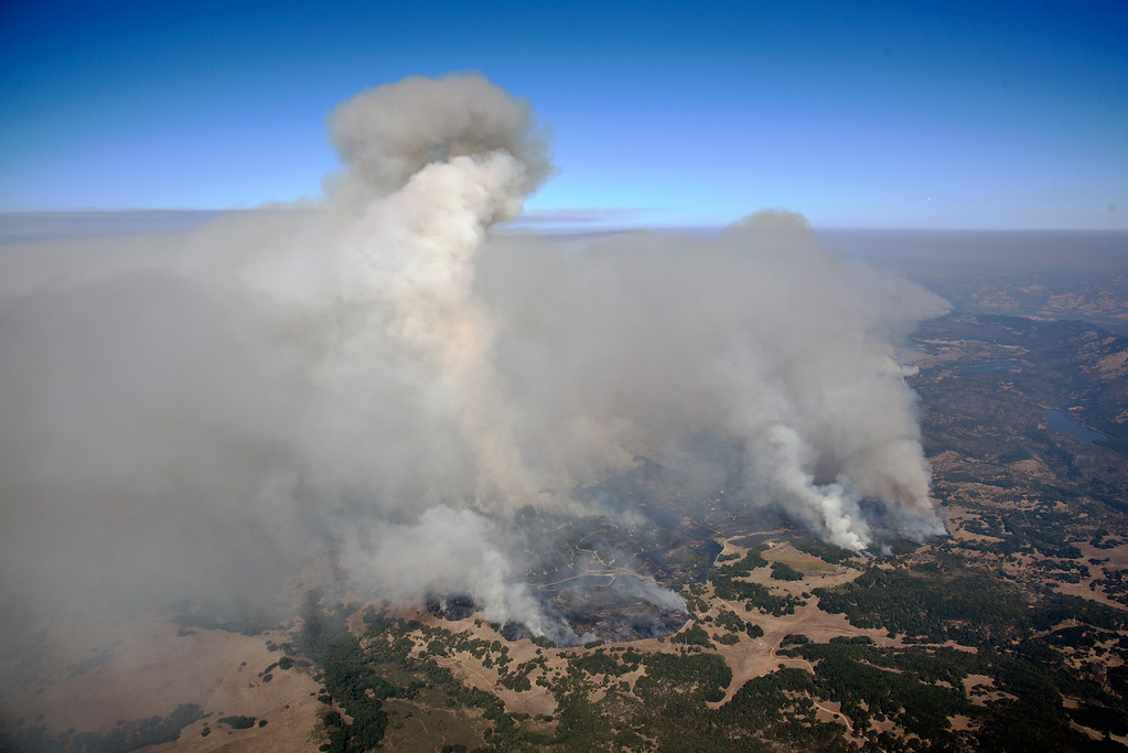 . Smoke rises as a wildfire burns in the hills east of Napa, Calif., Monday, Oct. 9, 2017. Wildfires whipped by powerful winds swept through Northern California sending residents on a headlong flight to safety through smoke and flames as homes burned. (Michael Short/San Francisco Chronicle via AP)