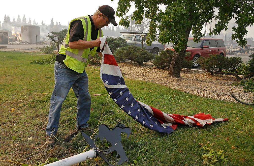 . Jim Cook, manager of the Journey\'s End mobile home park, picks up an American flag that fell from a flagpole during a fire on Monday, Oct. 9, 2017, in Santa Rosa, Calif. Wildfires whipped by powerful winds swept through Northern California early Monday, sending residents on a headlong flight to safety through smoke and flames as homes burned. (AP Photo/Ben Margot)