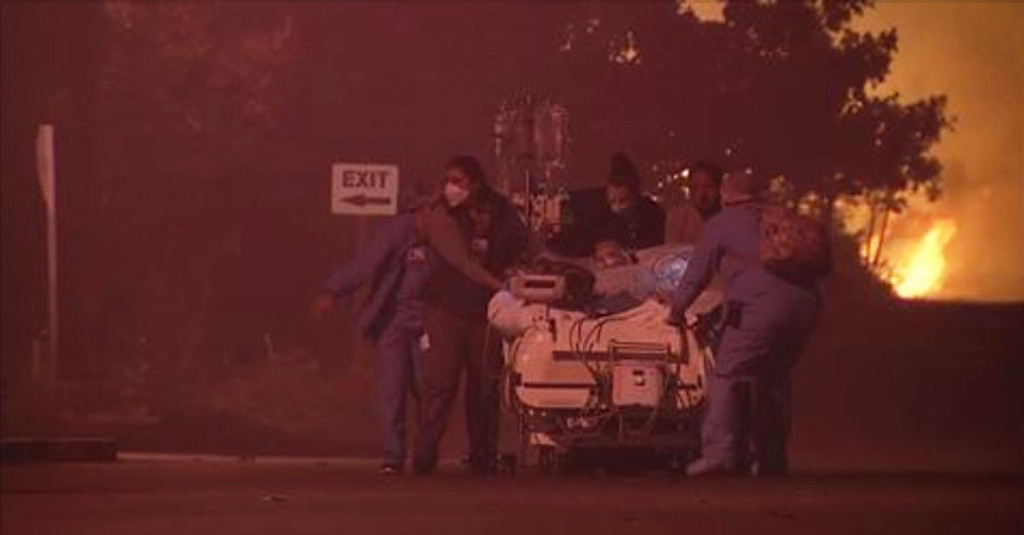 . In this image made from a video provided by KGO-TV/ABC7 News, hospital employees evacuate a patient from the Kaiser Permanente Hospital in Santa Rosa, Calif., after a wildfire fire forced evacuations Monday, Oct. 9, 2017. (KGO-TV/ABC7 News via AP)