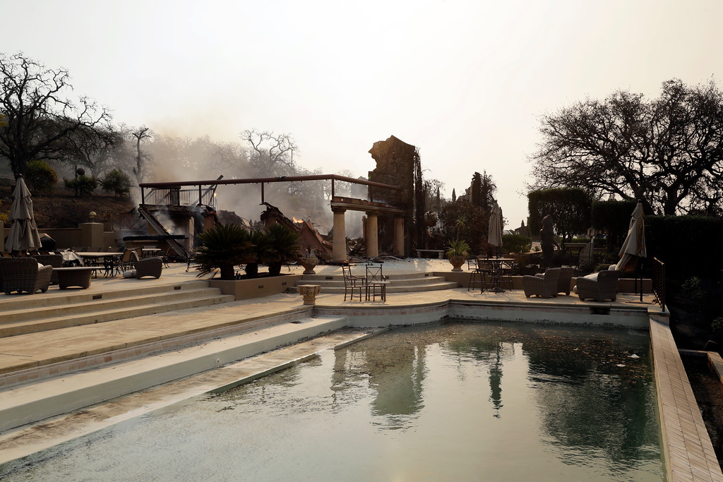 . A pool is seen in front of the fire-ravaged Signorello Estate winery Monday, Oct. 9, 2017, in Napa, Calif. Wildfires whipped by powerful winds swept through Northern California sending residents on a headlong flight to safety through smoke and flames as homes burned. (AP Photo/Marcio Jose Sanchez)