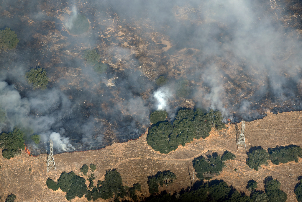 . Smoke rises as a wildfire burns near power lines in the hills north east of Napa, Calif., Monday, Oct. 9, 2017. Wildfires whipped by powerful winds swept through Northern California sending residents on a headlong flight to safety through smoke and flames as homes burned. (Michael Short/San Francisco Chronicle via AP)