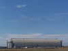 "There are two hangars, the east-west ""South"" hangar and the north-south ""North"" hangar. Each is 183 feet high, 296 feet wide and  1,000 feet long, covering an area of 7 acres."