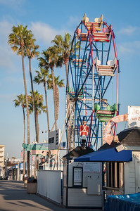 According to Wikipedia, The Fun Zone was built in 1936 by Al Anderson featuring a small beach and a 45' Ferris Wheel as the main attractions. In 1986, Jordan Wank rebuilt the entire area and re-opened it. In 1988, Doo & Sons owned the Balboa Fun Zone, but they walked away after not receiving zoning permits to develop the property into a mixed use of retail and housing. The property languished for several years and the area went into decline.  In 1994, the Balboa Fun Zone was purchased by former employee Joe Tunstall.  The Fun Zone consisted of a newly restored Carousel purchased in 1985, a #5 Eli Ferris Wheel, bumper cars, Drummer Boy, and the Scary Dark Ride There were also a few souvenir shops, restaurants and tour boat companies offering boat rides and narrated cruises  The Ferris wheel is a frequently photographed night landmark on the Balboa Peninsula.