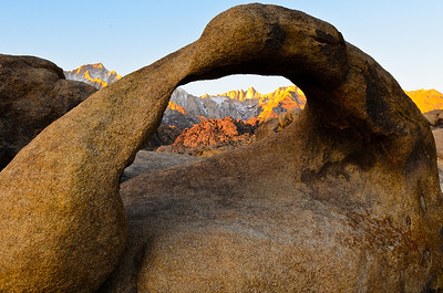 Mount Whitney in the rising sun framed by an stone arch in the Alabama Hills, California.