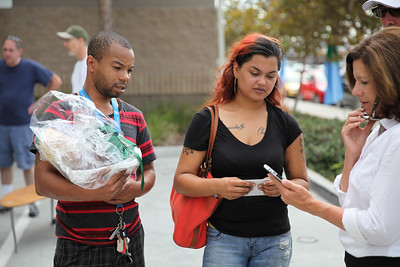 Volunteer and young couple using a cell phone to confirm directions to their apartment.