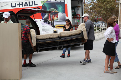 A young couple and a volunteer load a sofa into the truck.