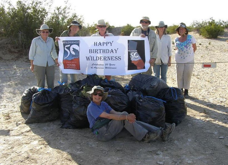This photo (from Mona Daniels) summarizes the trip's work--we pose with some of the 50+ bags we of weeds we picked from the dunes.