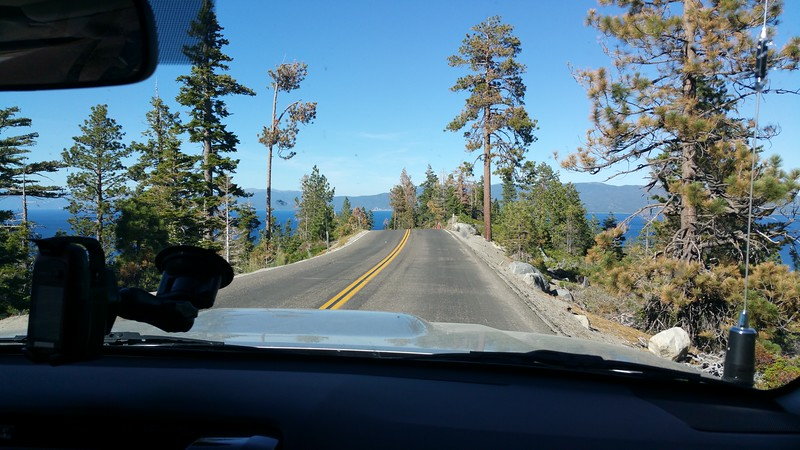 Traveling a narrow ridge line on CA Rt 89 high above Lake Tahoe. Lake Tahoe is visible on all sides as if the road drops into it up ahead. (Meredith)