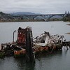 Rogue River Bridge on Hwy 101 in Gold Beach, Oregon.  Old boat rotting away in the foreground.