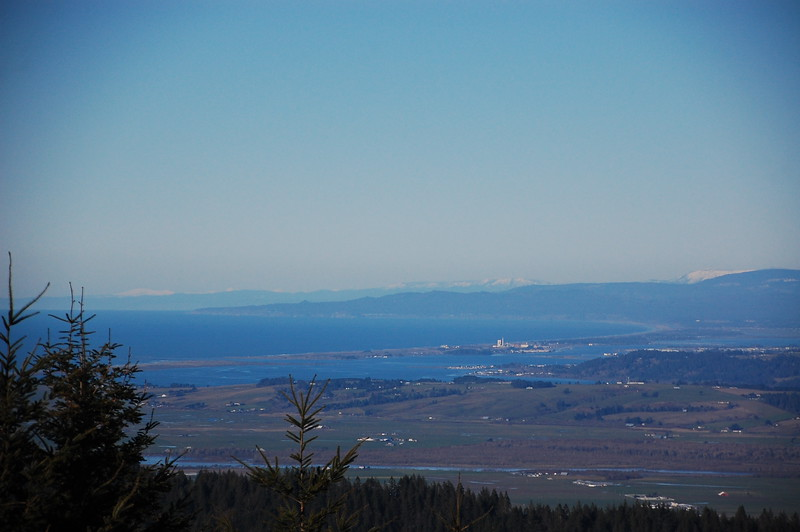 Ocean views and snowy mountains from Upper Bear River Road.  The river in the foreground is the Eel River as it empties into the Pacific Ocean.  Eureka is barely visible in the distance, just before the row of snow capped mountains.
