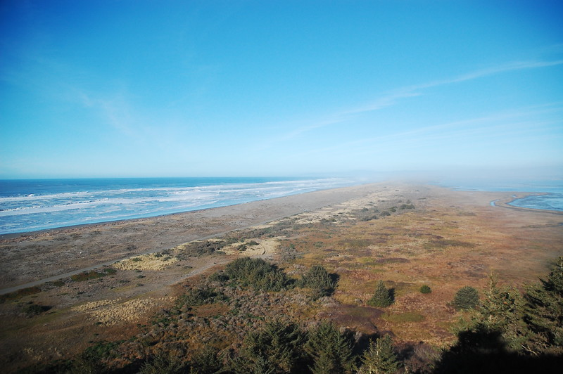 """The South Jetty on a foggy day, as seen from Table Bluff.  Far left is the Pacific Ocean and far right is Humboldt Bay.  To give a sense of scale, that straight strip running up the """"middle"""" of the jetty (from bottom left to the middle of the picture) is a 2-lane paved road."""