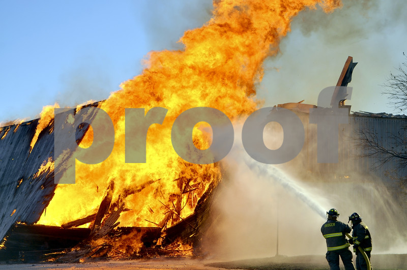 -Messenger photo by Chad Thompson<br /> <br /> Mike Magruder, a Badger volunteer firefighter, left, and Darrell Shirberoun, a Callender volunteer firefighter, get in some hose practice while the grain elevator continues to burn Sunday morning in Callender.