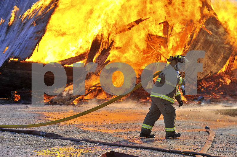 -Messenger photo by Hans Madsen<br /> <br /> Badger firefighter Mike Magruder drags a hose past the still burning remains of the old elevator.