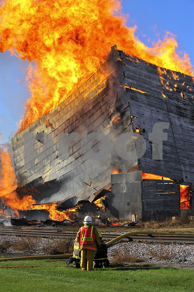 -Messenger photo by Hans Madsen<br /> <br /> As a crew watches from a distance, the north structure of the old wood grain elevator in Callender collapses Sunday morning about and hour and 15 minutes after the fire was lit during a controlled burn.