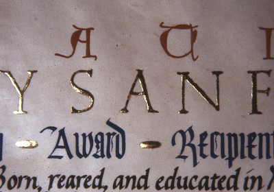 This is a detail of the citation for Teyy Sanford. he did not use his middle name and this marked a transition in these certificates from decoration initials to making the whole names in Gold. The letters of the name are burnished and the bullets in presentation are not.
