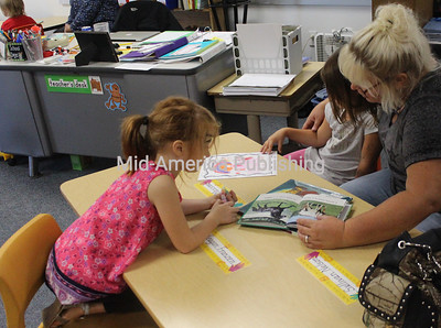 Charlotte Wangsness, Raelyn Massman and Lisa Massman take part in reading.
