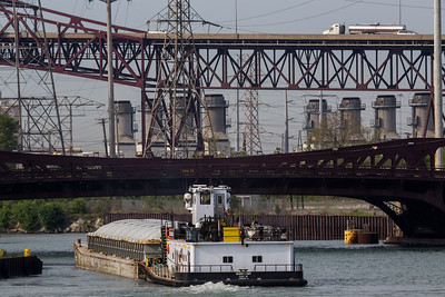 IMG_2732.jpg Tow boat with barge on the Calumet River heading south towards the 95th St. bridge and the Chicago Skyway bridge. 6/10/18
