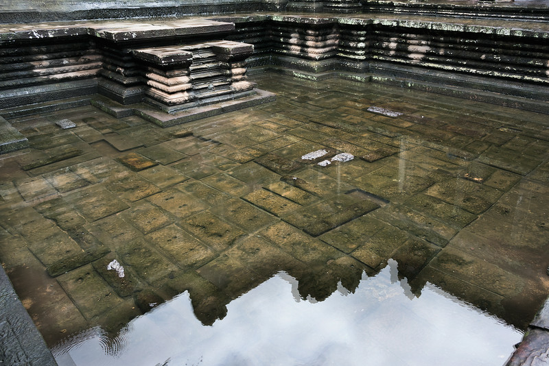 Reflection-of-Angkor-Wat-in-a-rain-pool-in-an-upper-level-courtyard,-Cambodia
