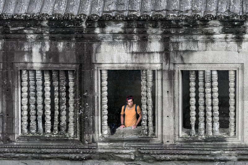 Rain,-rain-go-away,-man-sheltering-in-the-esplanade-of-Angkor-Wat,-Siem-Reap,-Cambodia