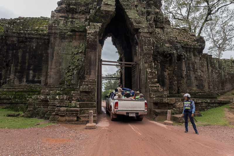 The-south-gate-of-the-Angkor-Thom-complex-with-police-woman-and-pickup-truck-loaded-with-people,-Cambodia