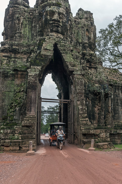 Tuk-tuk-passing-through-the-four-faced-south-gate-of-the-Angkor-Thom-complex,-Cambodia