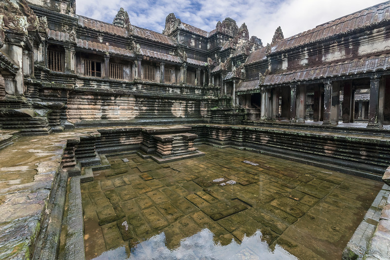 After-the-rain,-central-temple-of-Angkor-Wat-reflected-in-an-upper-level-courtyard,-Siem-Reap,-Cambodia