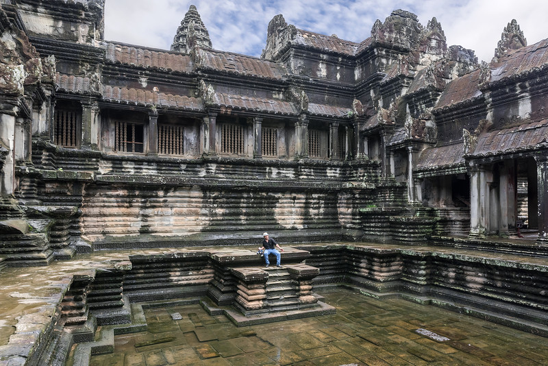 Hamming-it-up-with-a-camera-carrying-puppet-after-the-rain-storm,-inner-courtyard,-Angkor-Wat,-Cambodia