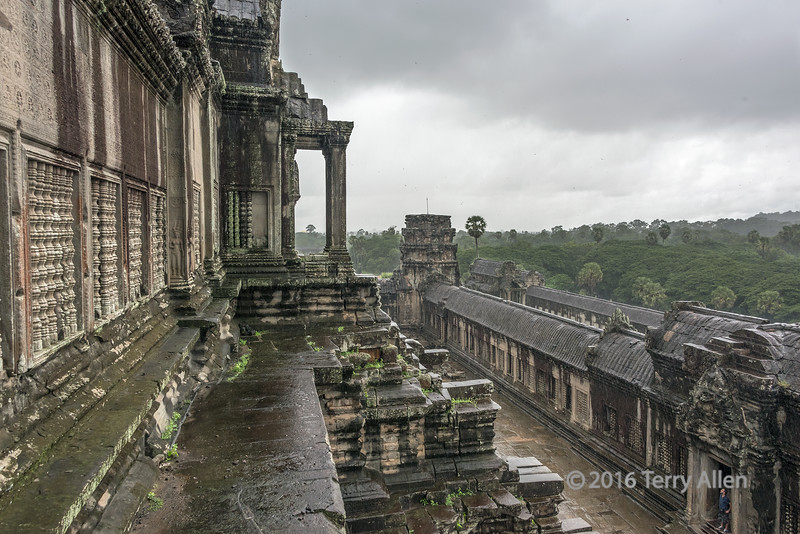 Center-temple,-inner-courtyard-in-the-rain,-birds-and-insects-in-the-sky,-Angkor-Wat,-Cambodia