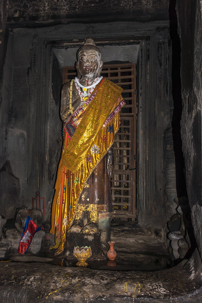 Statue-of-Buddha-drapped-with-a-decorated-gold-cloth,-under-the-central-dome-(inner-sanctuary)-of-Angkor-Wat,-Cambodia