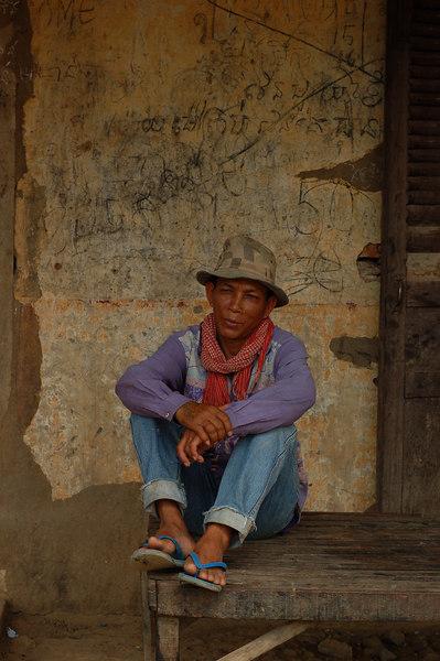 A man waits at the local (bamboo) train station.