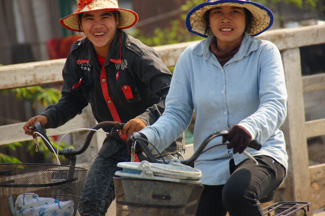 Two locals riding their bikes flashing big smiles - Battambang, Cambodia.  This is a travel photo from Battambang, Cambodia.