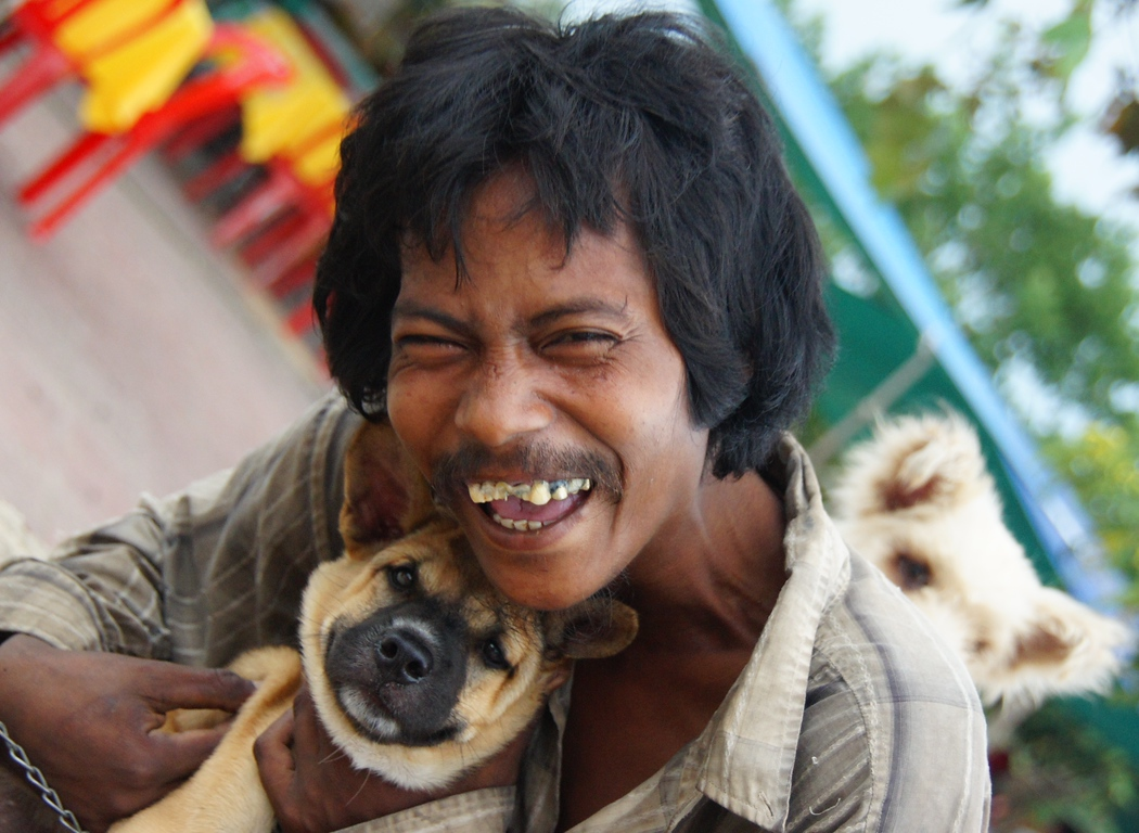 Today's daily travel photo is of a warm hearted Khmer man with his adorable dogs.  His radiant smile tells the whole story - Battambang, Cambodia.