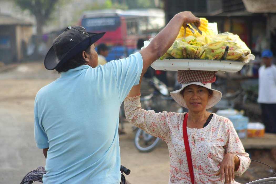 A Khmer lady carrying fruit on her head making a sale to a local man.  This is a travel photo from Battambang, Cambodia.