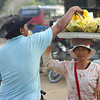 "A Khmer lady carrying fruit on her head making a sale to a local man.  This is a travel photo from Battambang, Cambodia. <a href=""http://nomadicsamuel.com"">http://nomadicsamuel.com</a>"