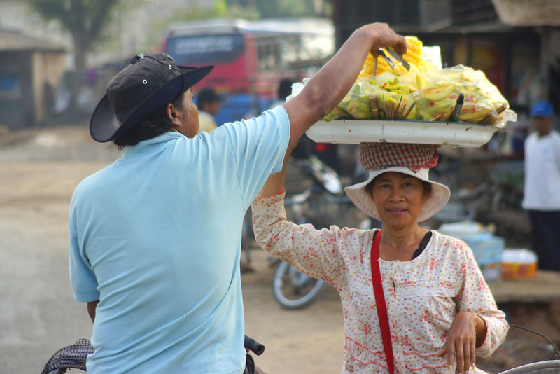 """A Khmer lady carrying fruit on her head making a sale to a local man.  This is a travel photo from Battambang, Cambodia. <a href=""""http://nomadicsamuel.com"""">http://nomadicsamuel.com</a>"""