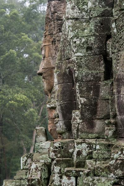 Compassionate-buddha-faces-(Lokesvaras)-in-the-rain,-Prasat-Bayon,-Angkor-Thom,-Siem-Reap,-Cambodia