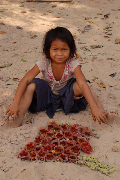 Cambodia, Angkor: A young girl displays her flowers at Neak Pean Temple.