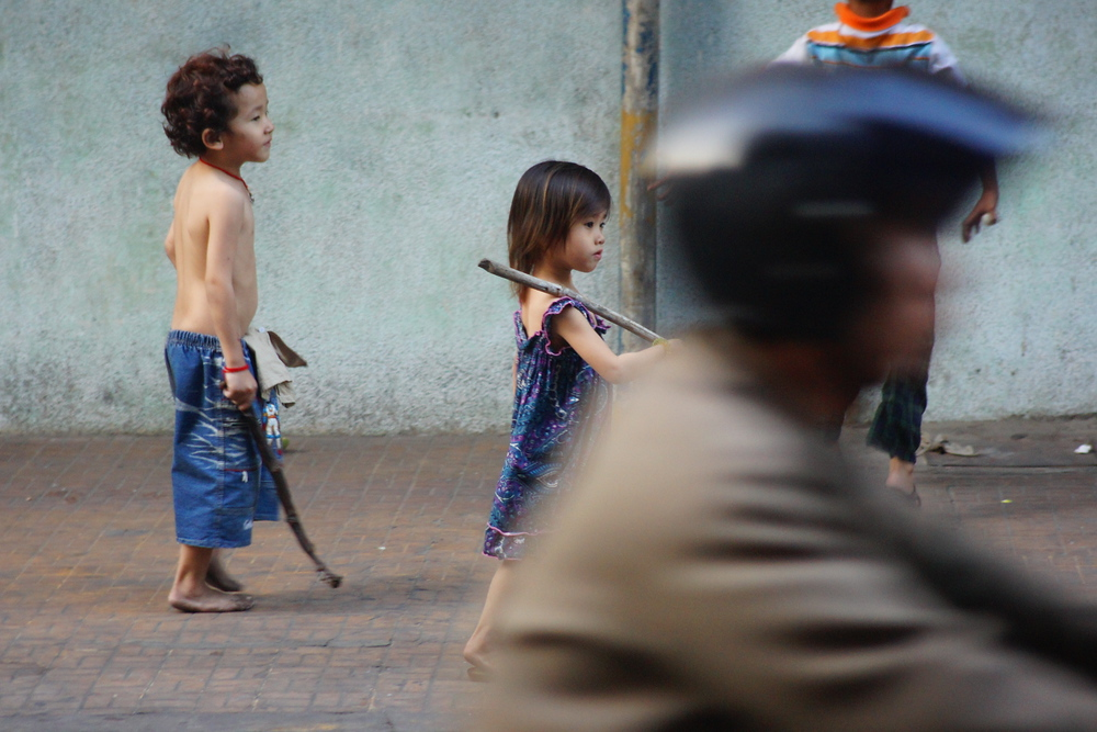 Today's featured travel image is of a cute Khmer boy and Khmer girl walking down a busy street where a motorcyclist zooms past them in Phnom Penh, Cambodia.
