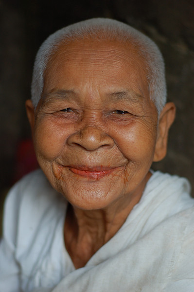 A smiling nun sitting in one of the towers of Bayon