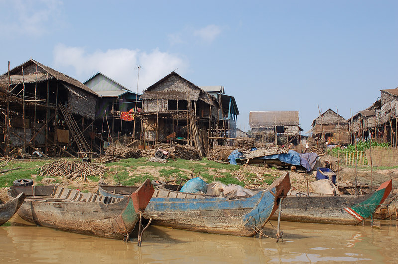 Fishing boats and typical houses line the river.