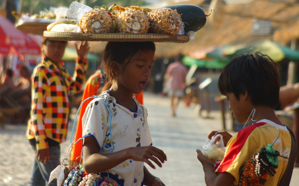Khmer children on the tourist beach carrying and selling fruit to farangs - Sihanoukville, Cambodia.  This is a travel photo from Sihanoukville, Cambodia.