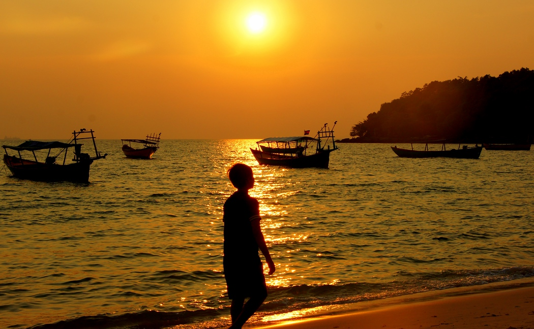 A Khmer boy walks along the beach as the golden sunset radiates the surroundings - Sihanoukville, Cambodia.  This is a travel photo from Sihanoukville, Cambodia.  To purchase this photo click on it or to view the rest of my gallery from Sihanoukville, Cambodia click here.
