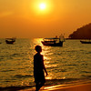 """A Khmer boy walks along the beach as the golden sunset radiates the surroundings - Sihanoukville, Cambodia.  This is a travel photo from Sihanoukville, Cambodia.  To purchase this photo click on it or to view the rest of my gallery from Sihanoukville, Cambodia click here. <a href=""""http://nomadicsamuel.com"""">http://nomadicsamuel.com</a>"""