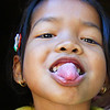 "A cheeky but undeniably cute Khmer girl sticks her tongue out at me while I'm visiting the Temples of Angkor, Cambodia. <a href=""http://nomadicsamuel.com"">http://nomadicsamuel.com</a>"