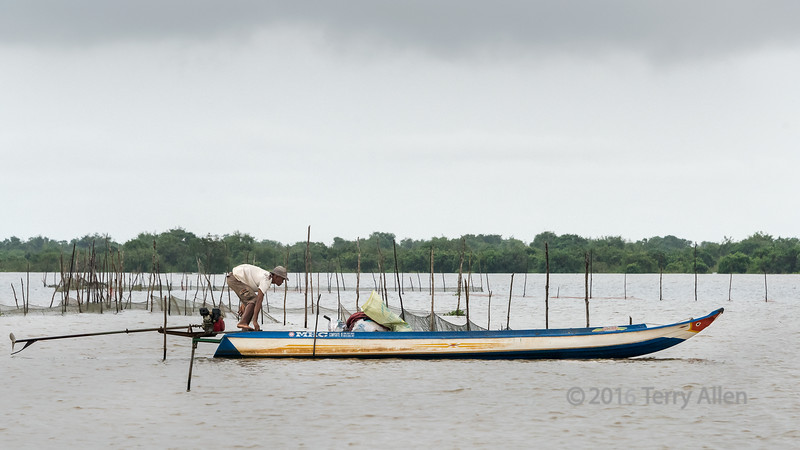 Fisherman-manoevering-his-long-tail-boat-near-his-fishing-nets,-monsoon-sesason,-Tonle-Sap,-Cambodia