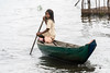 Girl poling a dugout canoe, Tahas River, Kampong Phluk, Cambodia