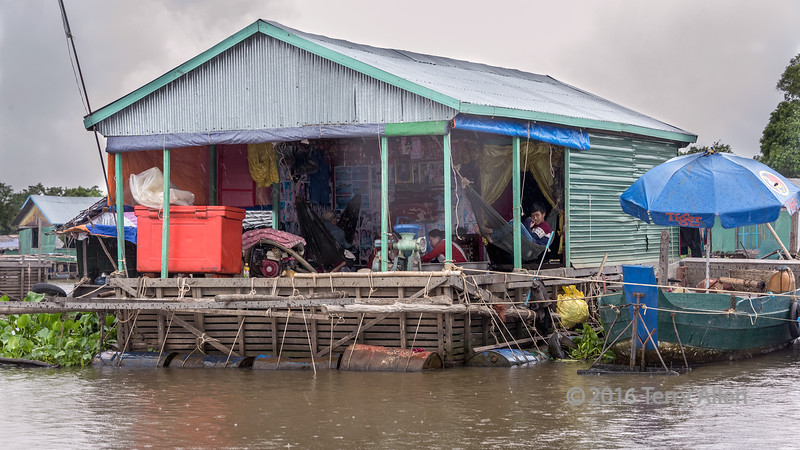 Woman-using-a-motorized-grinder-on-a-house-boat,-light-rain,-Tahas-river,-Tonle-Sap,-Cambodia