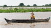 Boy-in-a-towed-dugout-canoe-with-protection-from-the-insects,-monsoon-season,-Tonle-Sap,-Cambodia