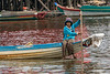 Girl paddling boat with red reflections, Tahas River, Kampong Phluk, Cambodia