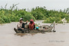 Fisherman-pulling-up-his-traps,-monsoon-season,-Tonle-Sap,-Cambodia